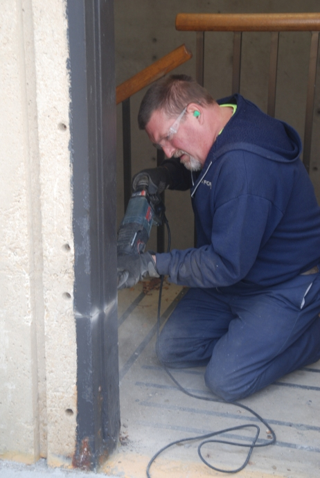 A Green Bay Installer begins taking out a portion of a frame so the new clamshell frame can be installed.